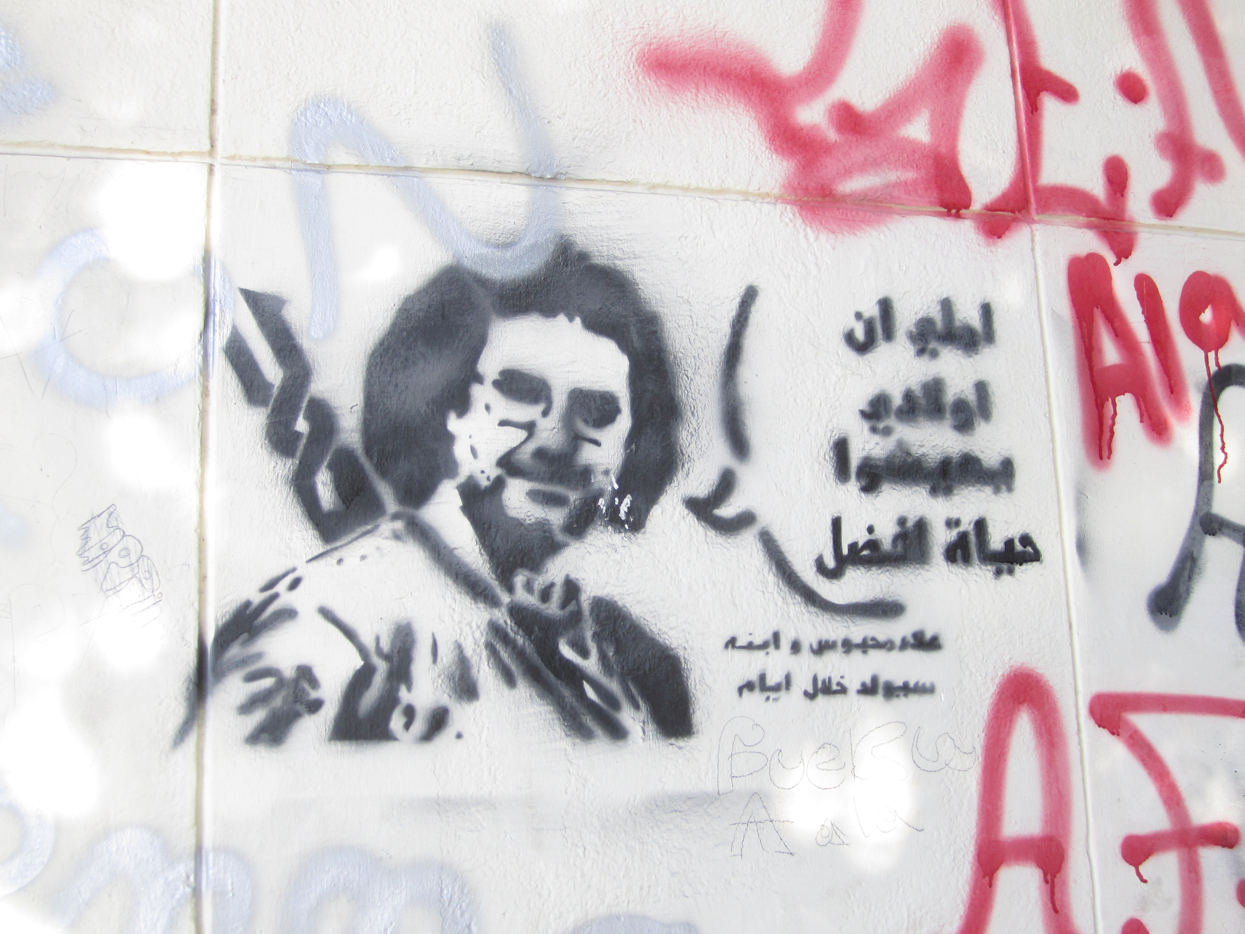 "Graffiti in Zamalek depicting Alaa Abd El Fattah (and the ""#nomiltrials"" symbol)"